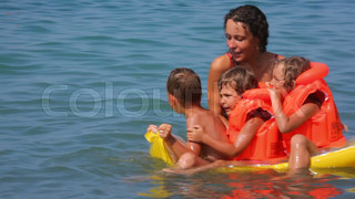 young woman with boy and two little girls on inflatable mattress has fun in sea