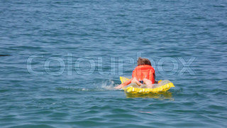 smiling young boy dressed in life jacket oaring on inflatable mattress in sea