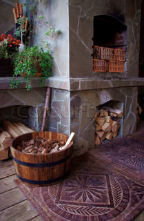 cosy veranda with fireplace, firewood and barrel full of cones