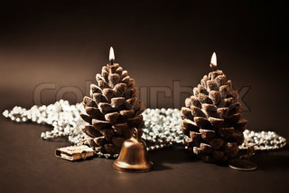 Two candles as a candle with christmas-tree decorations on  black background