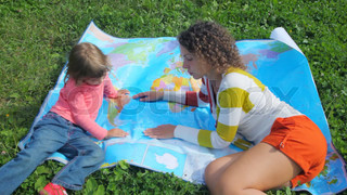 young woman and little girl lying on green grass, looks at political map