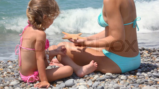 young woman and little girl sits on pebble beach with sea star