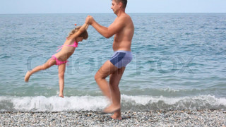 man rotating little girl on rocky beach, sea in background