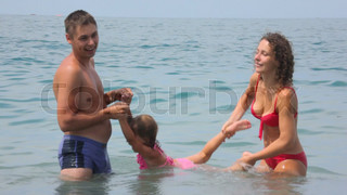 happy man and woman holds little laughing girl in sea