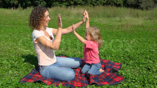 mother with daugher plays pat-a-cake sits outdoor in field