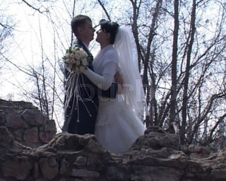 bride and groom kissing against naked trees