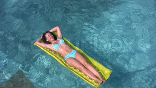 woman lies on inflatable mattress and oaring in swimming pool