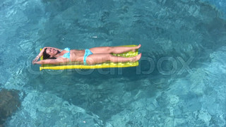 woman lying on inflatable mattress in water pool