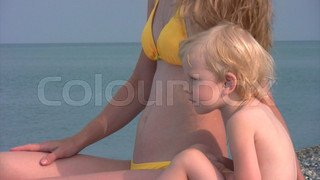 woman in bikini sits with little girl on beach