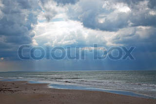 Dark clouds and sun rays at the beach