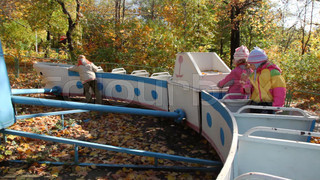boy pushing on carousel with girls on playground