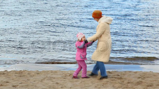 woman and girl dances on sandy beach