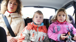 mum, daughter and son sit on back seat of car