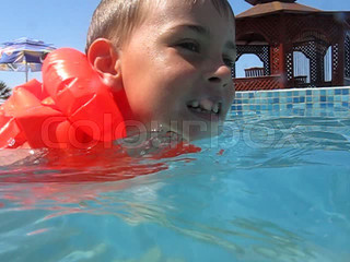 boy in inflatable jacket swims in water pool