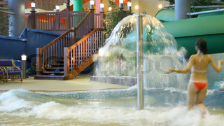 woman runs under fountain in a pool in indoor water park