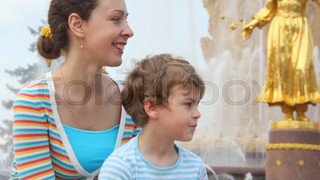 Mother and son sit near Fountain