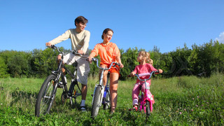 family with daughter sits on bicycles in field