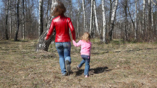 mother and daughter runs round the birch