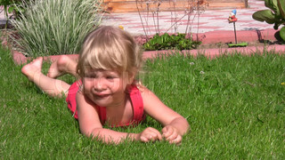 little girl lying on grass in outlet and dangles legs