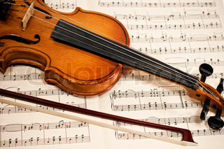 Old violin and bow on musical notes close up