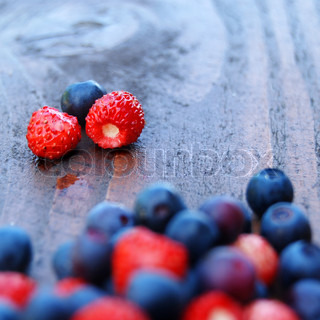 Forest berries on a wooden table. Blueberries and wild strawberries. Shallow dof, square format