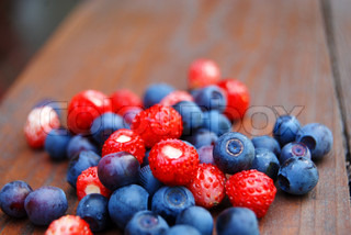 Close-up of blue and red forest berries, shallow dof, wooden background