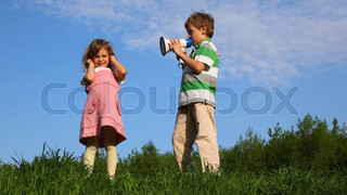 boy talking through megaphone with little girl plugging up her ears outdoor