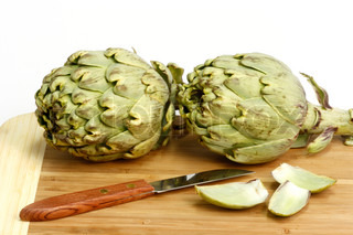 Preparation of fresh artichokes on a wooden plate