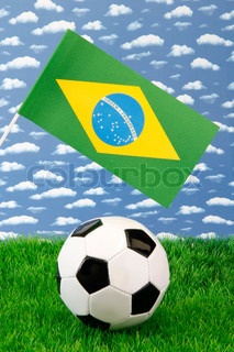 Football on grass with brazilian national flag over sky background