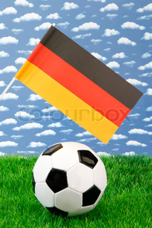 Football on grass with german national flag over sky background