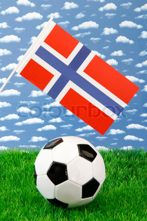Football on grass with norwegian national flag over sky background