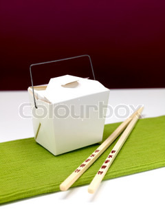 Chop sticks and a takeaway box on a kitchen bench