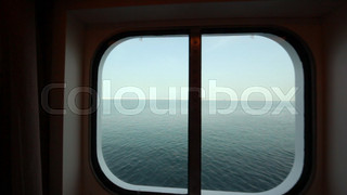camera moves to sidelight of passenger cabin in cruise ship