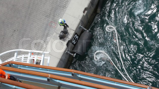 workers unbends mooring line of cruise ship from moorage