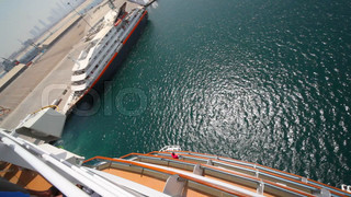 cruise ship moving pass moorage, top view from upper deck in Dubai, UAE.