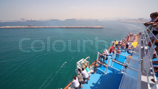 people on deck of cruise liner sailing out from Dubai, UAE.