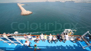 people stands on deck of sailing cruise ship in Dubai, UAE.