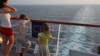 mother with son and girl stands on deck of ship