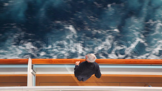 man stands on deck of cruise ship