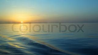 sunset above water cleaves by ship