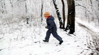 Boy with snowball runs round in snow forest