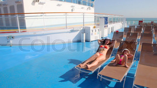 mother and daughter in bikini lying on deckchairs