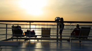 silhouettes of people on deck of cruise ship
