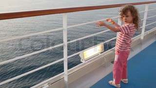 little girl stands on deck of cruise ship