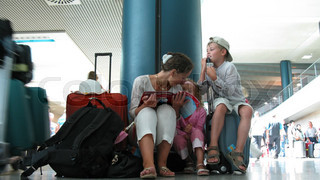 Mother with children sit about luggage in a hall of of the airport.