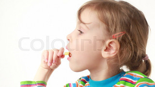 little girl eating lollipop in chicken form