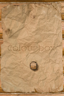 Old paper with a hole (against wooden background)