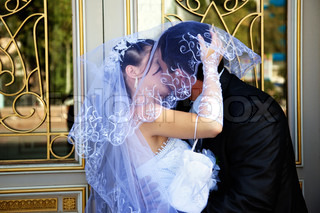 Close up of a bride's hand holding her veil while the couple kisses.