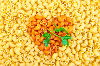 Texture of the yellow and orange pasta in the shape heart, a green sprig of parsley