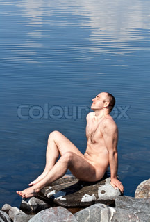 wet naked man sitting on a rock against the lake and relax